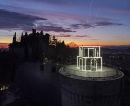 Fulgida, Massimo Uberti. Opera ritraente una struttura di neon situata su castello di Brescia al tramonto