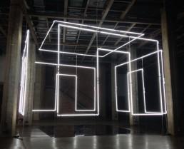 In your eyes, Massimo Uberti. Opera ritraente una stanza di neon sospesa a mezz'aria all'interno di un capannone