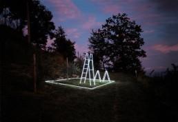Linee di costruzione, Massimo Uberti. Opera ritraente scale di neon situate in un bosco al tramonto