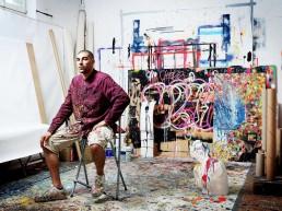 Omar Hassan. Foto ritraente Omar Hassan nel suo studio con dietro svariate sue opere